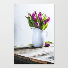 A bouquet of purple tulips in a vase against the wall Canvas Print