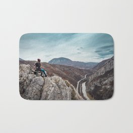 Girl sitting on the bench on the edge of the canyon with amazing view in front of her Bath Mat