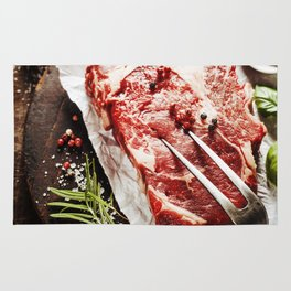 Raw beef steak with meat fork and ingredients on wooden background Rug
