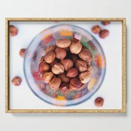 Purified hazelnut in a transparent glass with colored patterns, top view Serving Tray