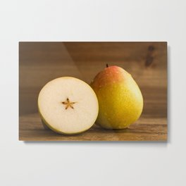 One pear and a cross section of another pear on table Metal Print