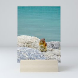 Digital Painting of a Cute Chipmunk sitting on a Rock in front of Lake Louise, Alberta Mini Art Print