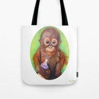 budi Tote Bags featuring Budi the Rescued Baby Orangutan by Alina Bachmann