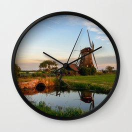 Windmill in a countryside landscape in Holland at sunset Wall Clock