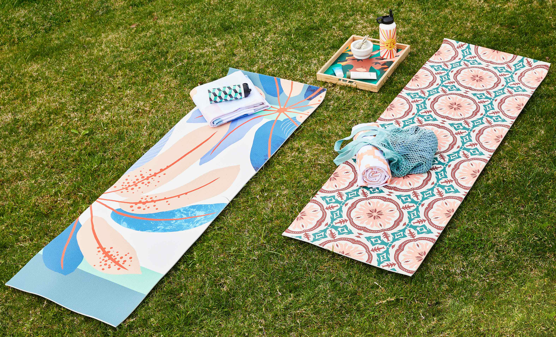 pastel colored yoga mats on a grassy lawn