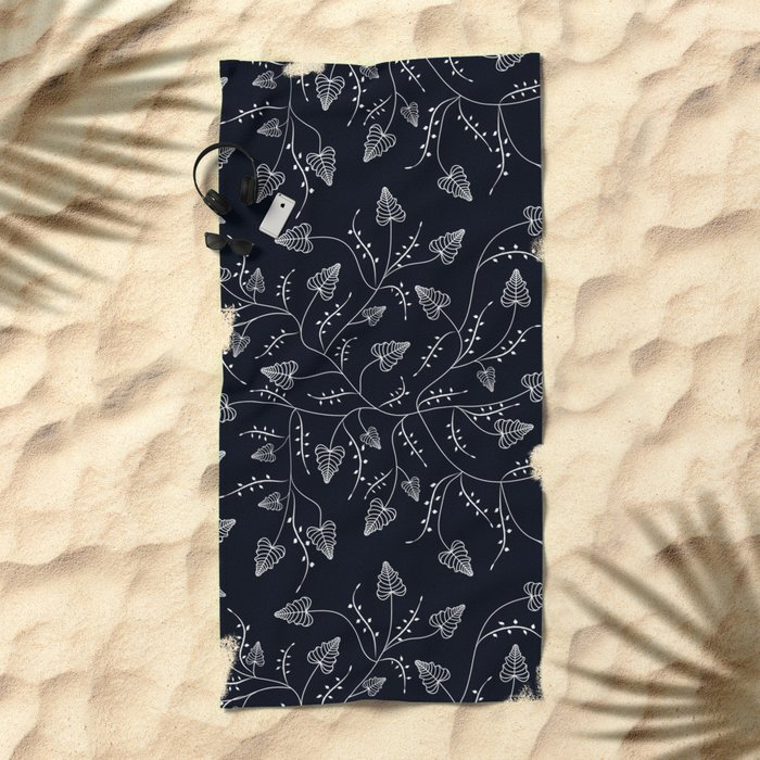 Delicate leaves on a black background . Beach Towel