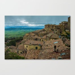 Mountain village with reddish roofs. Cloudy sky over the mountains. Canvas Print