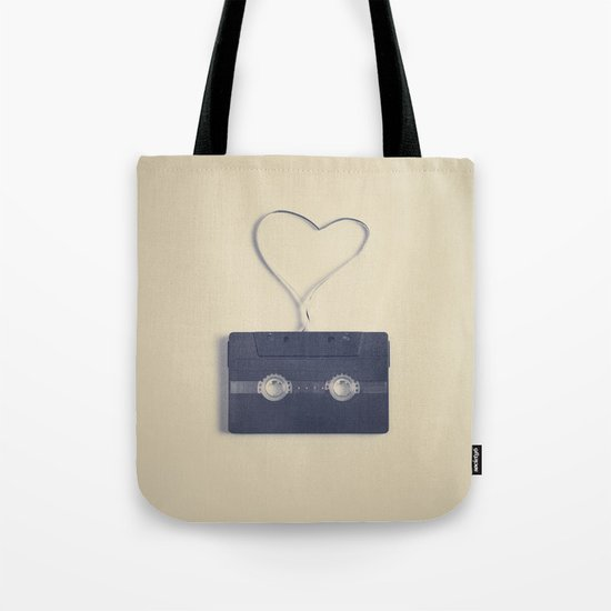 Retro black music cassette and heart shaped tape on beige background Tote Bag