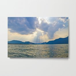 Rays of sunlight shining through the clouds down on a calm ocean Metal Print