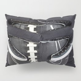 Black gloved hands holding a black American Football Pillow Sham