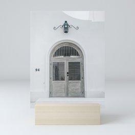 CLOSED GREY WOODEN DOOR BELOW BLACK LIGHT SCONCE Mini Art Print
