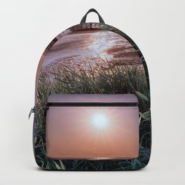 Minimal seascape with grass, sand and a river flowing into the sea. Backpack