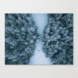 Man lying in the snow on a frozen lake in a winter forest - Landscape Photography Canvas Print