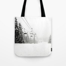 Lifts waiting for action in the snow Tote Bag