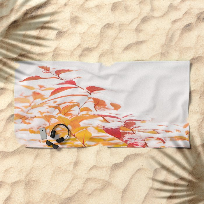 Snow covered red leaves Beach Towel