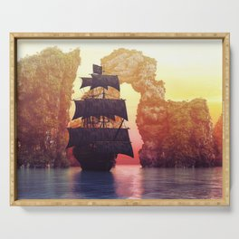 A pirate ship off an island at a sunset Serving Tray