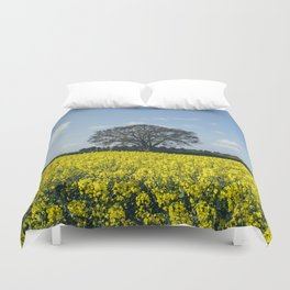 Field of Rapeseed (Canola) and tree against a sunlit blue sky. Norfolk, UK. Duvet Cover