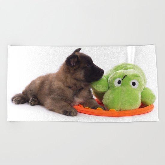 Puppy cuddling green toy Beach Towel