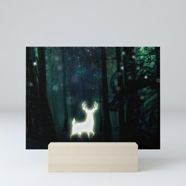 Dark Green Forest with Glowing Reindeer and Shimmering Lights Mini Art Print