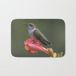 Humming bird resting on a flower Bath Mat