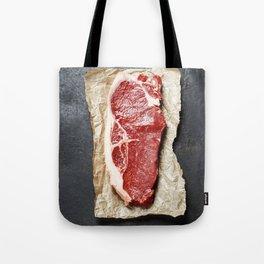 Raw beef steak on a dark slate background Tote Bag