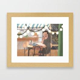 Female Emirati reading a book in a coffee shop Framed Art Print