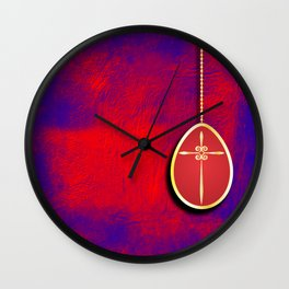 Gold cross in red egg hanging against a rich red and purple Wall Clock