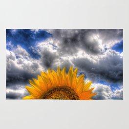 Clouds drift over a sunflower field Rug