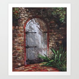 Decorative door in archway set in stone wall surrounded by plants Art Print