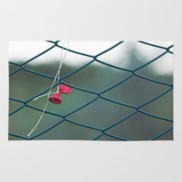 Deflated red balloon on fence net Rug