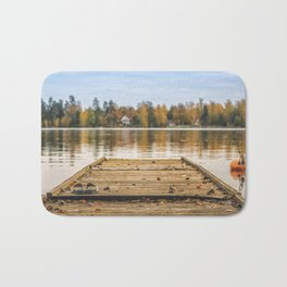 Pictuer of old slippers on the wooden pier with beautiful autumn background. Bath Mat