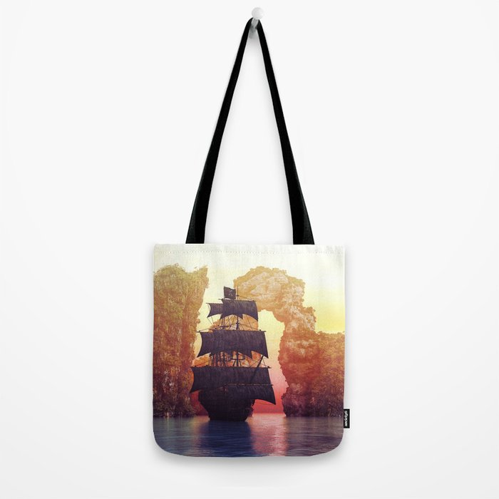 A pirate ship off an island at a sunset Tote Bag