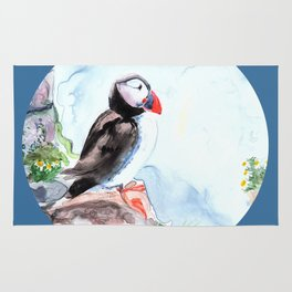 Puffin sitting on a rock with a blue background Rug