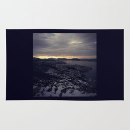 Winter morning, view of a city, sea and mountains Rug
