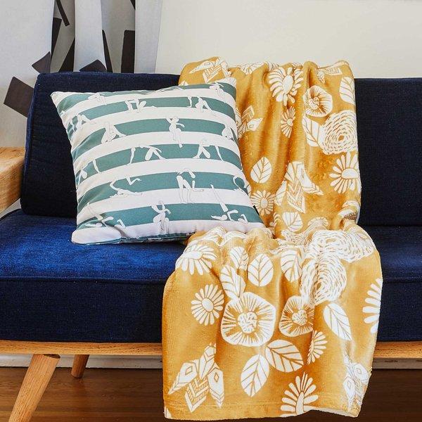 green throw pillow and yellow throw blanket on sofa