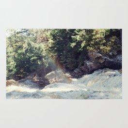 a rainbow at the falls Rug