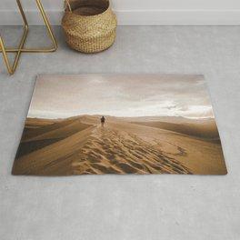 Young woman treks across sand dunes in the Hucachina desert, Peru Rug