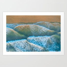 Looking down at ocean waves roll and crash into the shore at sunrise Art Print