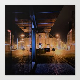 nightly street scene with lights reflecting in store front Canvas Print
