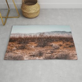 Desert and wind turbine with mountain view at Kern County California USA Rug