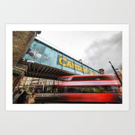 Long exposure of the painted Camden Lock bridge across Camden High Street with a blurred red London Double Decker bus passing beneath it Art Print