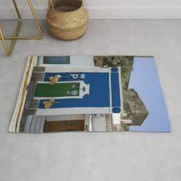 a small blue building by castle walls in an Alentejo street, Portugal Rug