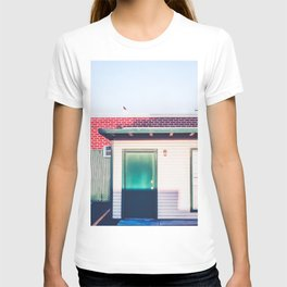 green wood building with brick building in the city T-shirt