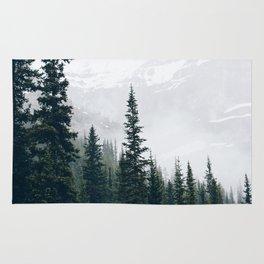 Evergreens in the fog Rug