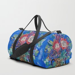 Painterly Bouquet of Proteas in Greek Horse Urn on Blue Duffle Bag
