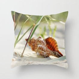 big shell in the sand, in the green of the beach-oats Throw Pillow