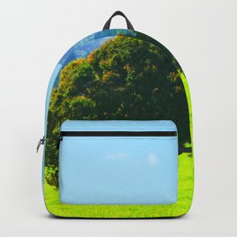 green tree in the green field with green mountain and blue sky background Backpack