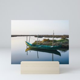 Weathered small boat close to peaceful shore in a beautiful lagoon on bright day. Mini Art Print