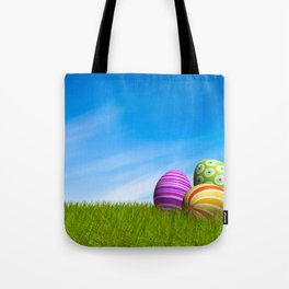 Decorated Easter eggs in the grass under a blue sky Tote Bag