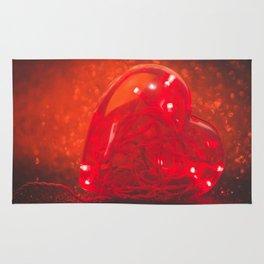 Led lights inside plastic heart with defocused red glitter background.  Rug